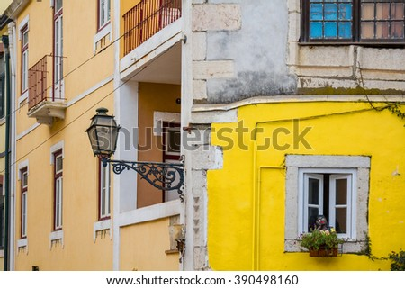 old traditional house in the historic center of lisbon with a street lamp and an open window with potted flowers