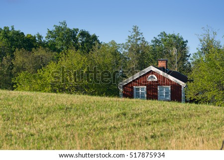 Old traditional red painted farmhouse in Sweden hidden behind hills. In the foreground landscape with meadows