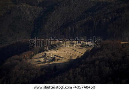 old traditional Romanian barn or shack with straw roof on a meadow lit by sun - stock photo