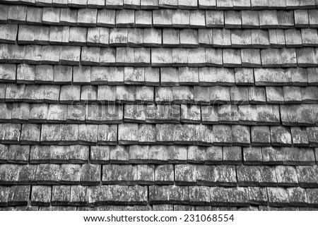 Old traditional wooden tiled roof. Aged photo. Black and white. - stock photo