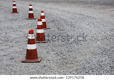 Old Traffic cone used in gravel street - stock photo