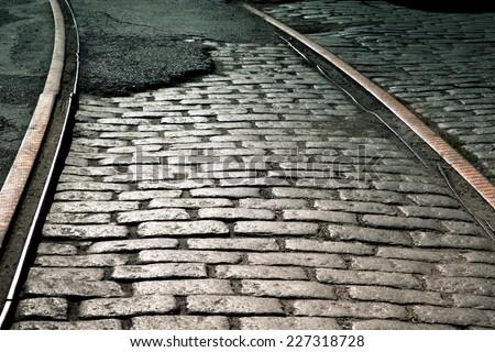 Old train rails on cobblestone street - stock photo