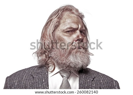 Old tramp in a suit with long hair and beard - stock photo