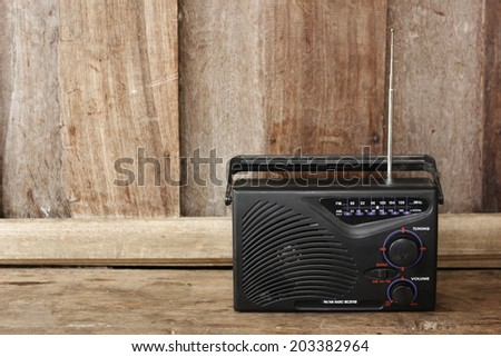 Old transistor radio on wooden background - stock photo