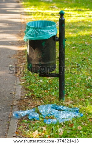 Old trash can in park and heap of plastic bottles, concept of environmental protection, littering of environmental