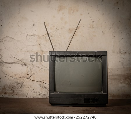 Old tv on wood with grunge background - stock photo