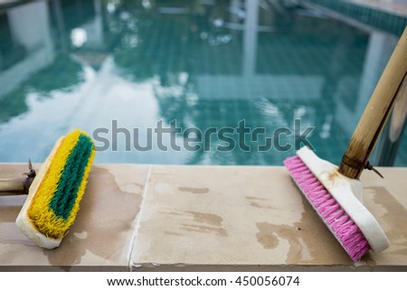 Old two plastic brush on poolside, swimming pool cleaning tool