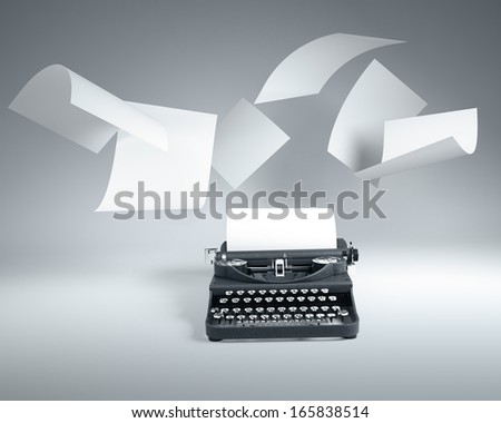 Old type writer with paper sheets flying - stock photo