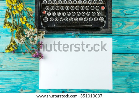 Old typewriter and a blank sheet of paper, retouching author writer. Blue wooden table dry flowers. Top view. The creative process of writing a new novel