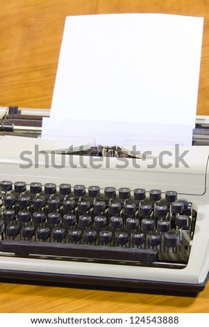 old typewriter and clean sheet of paper