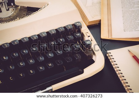 Old typewriter and old book on black table background vintage color
