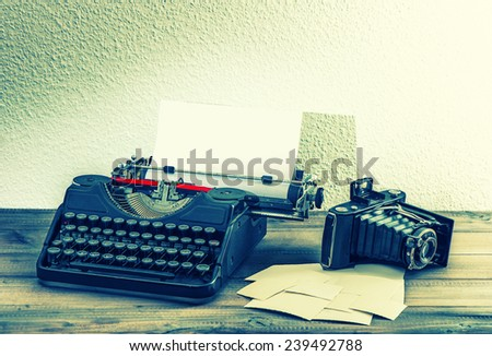 old typewriter and vintage photo camera on wooden background. retro style toned picture - stock photo