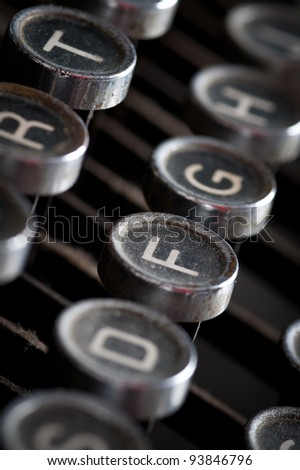 Old typewriter keyboard with silver and black round keys background. - stock photo