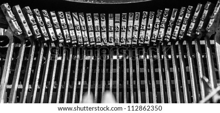 Old Typewriter keys - faded color and rusted with focus on center keys and  shallow DOF - stock photo