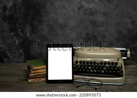 Old typewriter, old books, reading glasses and an self-designed E-Reader with blank display