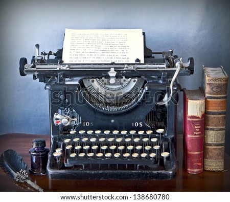 Old typewriter on a wooden desk, with a paper sheet of faded characters, old books, ink and pen with grunge background - stock photo
