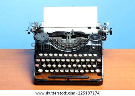 Old typewriter on wood on a blue background - stock photo