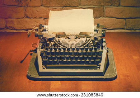 old typewriter on wooden table, retro filtered, instagram style - stock photo