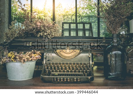 Old typewriter vintage ornaments and vases of dried flowers on a wooden table. - stock photo