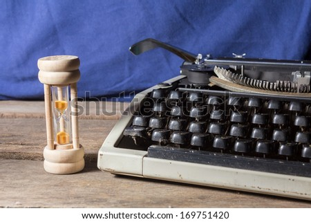 Old typewriter with hourglass  - stock photo