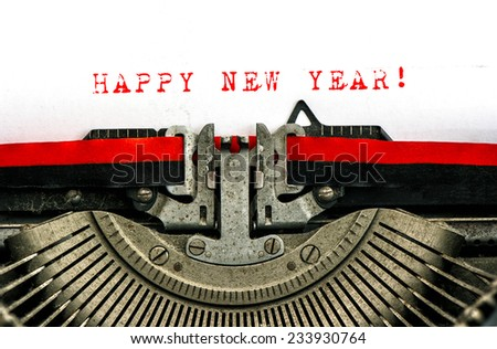 Old typewriter with sample text HAPPY NEW YEAR! Red words on white paper. retro style toned picture - stock photo
