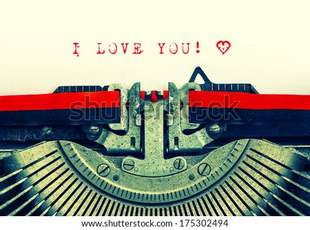 Old typewriter with sample text I LOVE YOU! Red words with heart on white paper. Retro style toned picture - stock photo