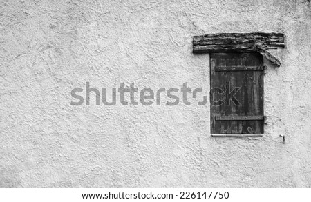 Old typical Mediterranean house with stucco wall and closed wooden shutters. Aged photo.  Black and white. - stock photo
