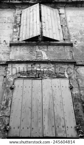 Old typical Mediterranean house with wooden shutters and stucco wall  (Arles, Bouches-du-Rhone, Provence-Alpes-Cote d'Azur, France) Aged photo. Black and white. - stock photo