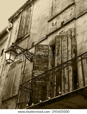 Old typical Mediterranean house with wooden shutters and stucco wall with peeling paint (Arles, Bouches-du-Rhone, Provence-Alpes-Cote d'Azur, France) Aged photo. Sepia. - stock photo