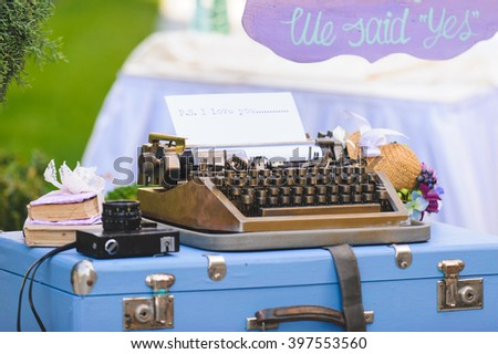 old typing machine with hat and camera on blue suitcase - stock photo