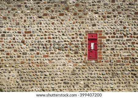 Old UK Post Box embedded in a flint stone wall. Marked VR from Queen Victoria 1850's to 1901 and still in use. - stock photo