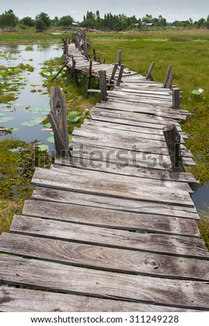 Old unfinished wood bridge over water