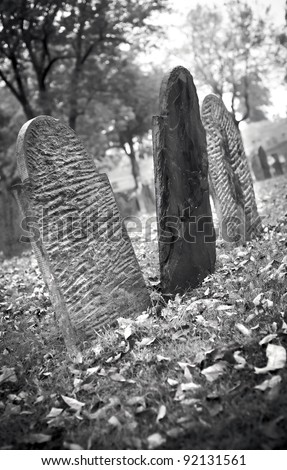 Old unmarked gravestones in an old cemetery during autumn in black and white. - stock photo