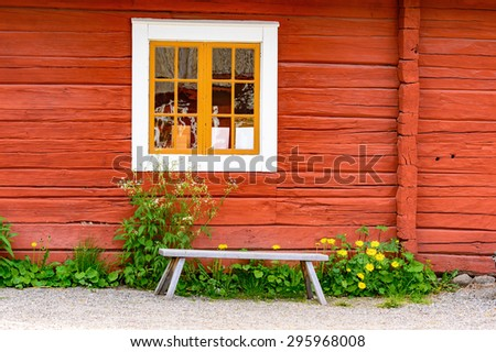 Old unpainted wooden bench under a white window on red house. - stock photo