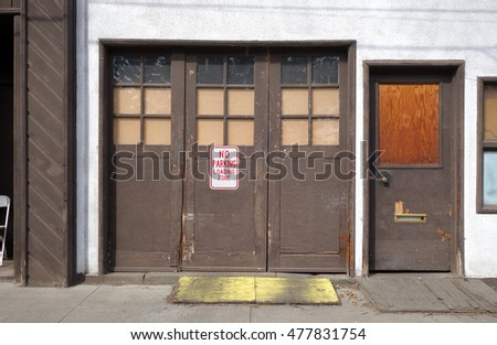 old urban garage with no parking sign on door