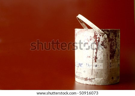 Old used bucket in a brownish red background - stock photo