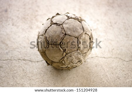 Old used football or soccer ball on cracked asphalt - stock photo
