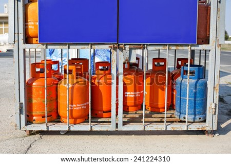 Old used gas bottles cylinders storage. Propane, butane. Bright orange and blue colors. Empty space for your text.  - stock photo