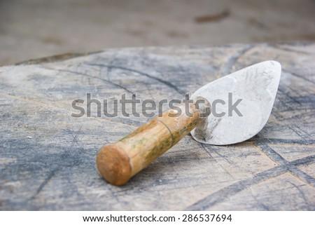 Old used metal masonry trowel - stock photo