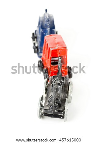 Old, used metal toy train with locomotive and wagons over white background