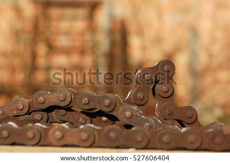Old used rusty chain links, on wood texture pallet surface. Warm natural autumn sunlight