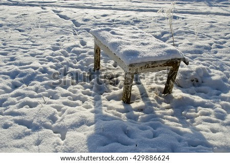 old used wooden table in farm garden yard in winter snow  - stock photo
