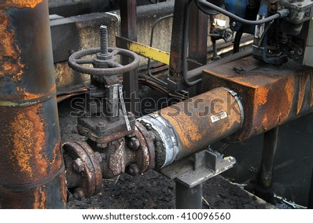 Old valve and lagged pipework on industrial site.