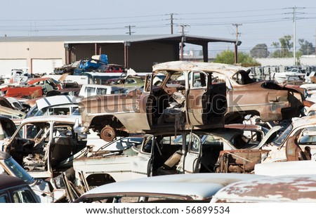 old vehicles in an auto salvage yard being recycled for parts and scrap metal