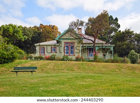 Old victorian house and bench on lawn before it, Auckland, New Zealand. - stock photo