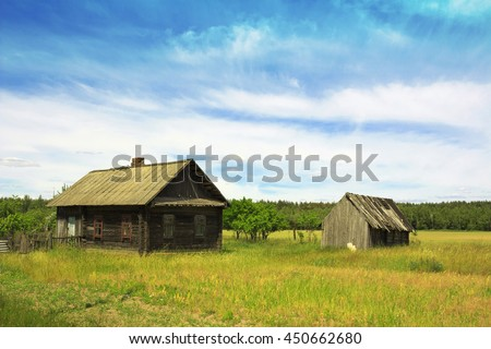 Old village house in a field - stock photo
