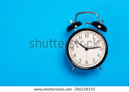 Old vintage alarm clock standing on the blue paper surface