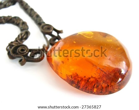 Old vintage amber pendant on white - stock photo