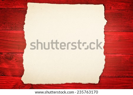 Old vintage beige paper on red wooden planks - stock photo