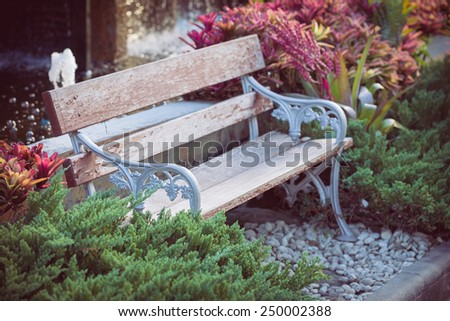 old vintage bench in flowers garden - stock photo